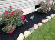 black mulch for garden with decorative pink flowers green grass and stones