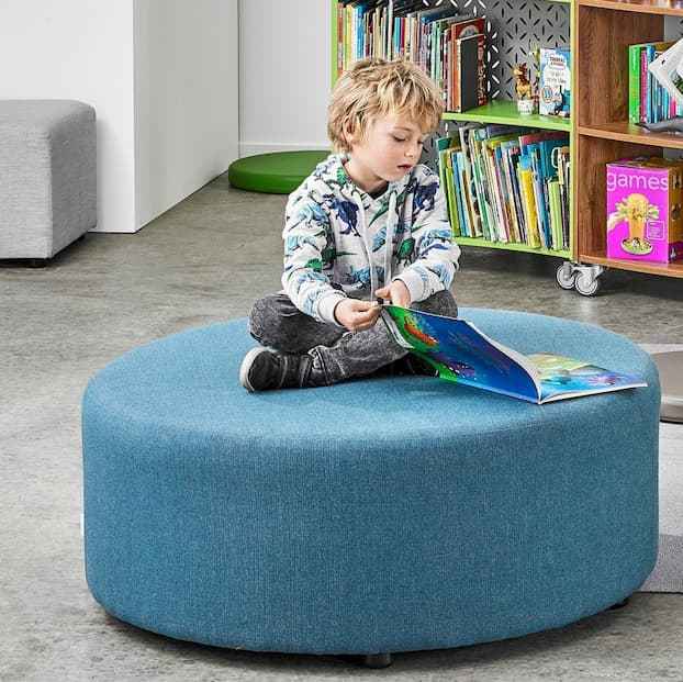 little boy sitting on a blue ottoman and looking in the book