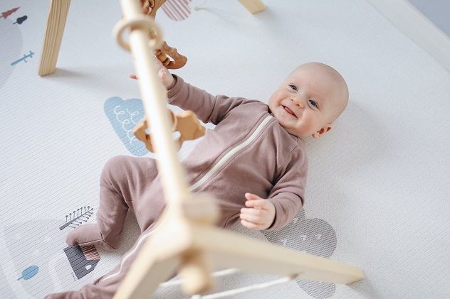 picture of a baby on the floor on a playmat and gym