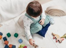 picture of a baby on the floor playing with a wooden toys